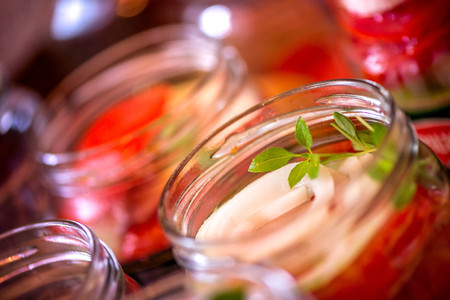 Canning fresh tomatoes with onions for winter in jelly marinade. Macro shot of basil leaves on top of a red ripe tomato slice being put in jar.