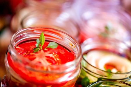 sterilized: Canning fresh tomatoes with onions for winter in jelly marinade. A shot of basil leaves on top of a red ripe tomato slices and onion rings being put in jar. Stock Photo