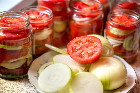 Canning of fresh tomatoes with onions for winter in jelly marinade. A shot of onion rings and red ripe sliced tomato on plate, being put in a jar for winter Stock Photo