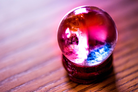 Fortune telling. Love, money, luck, success. Macro shot of purple, blue and turquoise chrystal ball on a wooden pad, with sun reflections, bubbles and a rainbow in it,standing on a pine dining table.