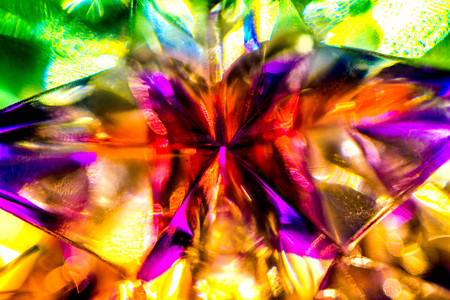 Abstract, blurry, vibrant and colorful background. Macro shot of a Christmas star on a lit Christmas Tree Stock Photo