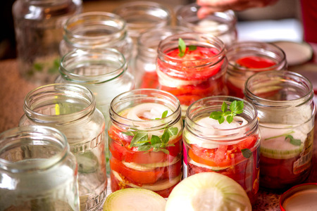 Canning fresh tomatoes with onions for winter in jelly marinade. A shot of basil leaves on top of a red ripe tomato slices and onion rings being put in jar. Stock Photo