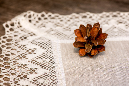 white trim: Macro shot of a pine cone on a linen tablecloth with crochet white lace trim on a wooden table