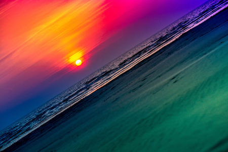 Golden, colorful, abstract sea sunset view at horizon, vibrant sky landscape and waves in the water. Sunrise reflection in nature with sun in clouds above black, dark ocean. Orange, blue, purple, red. Stock Photo