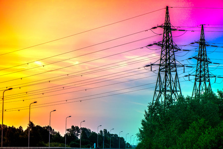 A silhouette of high voltage electrical tower structure next to highway road in early morning, during sunrise. Electricity tower, city lights, electric and power line. Sunset sky background. Road trip