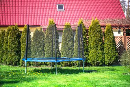 Een openlucht blauwe en zwarte springtrampoline met veiligheidsnet in binnenplaats, in tuin op zonnige de zomerdag. Genieten van vakantie in een pension op het platteland. Groene jeneverbesbomen op een rij. Sportactiviteiten
