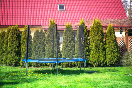 An outdoor blue and black jumping trampoline with safety net in backyard, in garden on sunny summer day. Enjoying vacation at guest house on countryside. Green juniper trees in a row. Sport activities