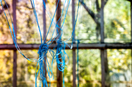 Macro shot of tangled blue ropes, threads in abandoned greenhouse, factory. Scary building with glass walls. Middle of nowhere. Lost, abducted person was tied in ropes. Sun rays, colorful background