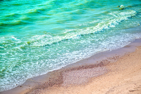 Serene seashore beach. Floating water, waves and white foam around big rock in the salty water. Flood tide at the ocean. Summer vacation at the seaside. Restore energy and enjoy calmness in nature