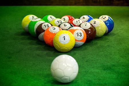 Coup de balles de piscine pied, debout sur la table verte. Foot Pool est la combinaison hybride de la piscine et du football. Big boules de billard. Banque d'images - 83755234