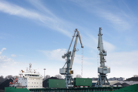 freight train: Shot of two old, rusty, grey port cranes with big hooks, lifting cargo in ship on clear blue sky background. Equipment for unloading ships and barges. Preparing for export world wide. Work at harbor