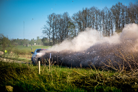 Rally car driving rapidly, on racing track. Flying dust, rocks, sand, thrown by tires, spinning extremely fast. Driver is trying to set lap record. Car driving fast on country road. Entertaining event Stock Photo