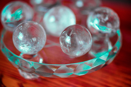 Macro shot of transparent crystal balls with colorful ornaments and sun reflections in it, on turquoise glass pad standing on a pine dining table.Fortune telling. Love, money, luck, success.