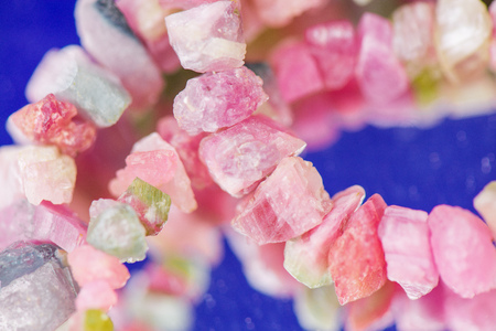 Macro shot of watermelon tourmaline crystals in necklace. Natural, rough, unpolished stones. Beautiful, pink and green gemstones on blue background Stock Photo