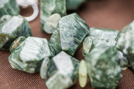 energy healing: Macro shot of serpentine crystals in necklace. Natural, beautiful gemstones. Serpentine stone has a strong energy known to stimulate the arousal of the kundalini energies
