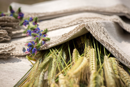 Shot of linen towels, tablecloths, napkins with lace trim, barley and flowers .