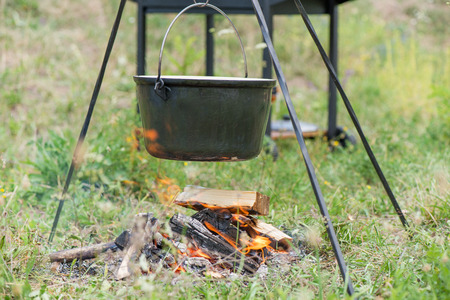 Boiling, hot goulash soup with meat, paprika, potatoes, onion, carrots is the traditional dish of Hungarian cuisine. Meat stew being prepared in crock pot on open fire. Picnic at the weekend in nature