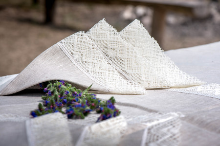 Shot of linen napkins with snow white crochet lace trim and blue flowers