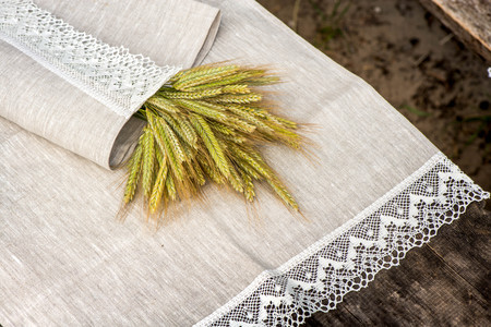 Shot of barley and flowers rolled in a linen towel with snow white lace trim.