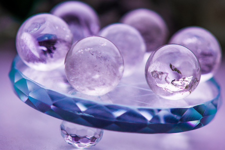 Macro shot of transparent crystal balls with colorful ornaments and sun reflections in it, on turquoise glass pad. Fortune telling. Love, money, luck, success