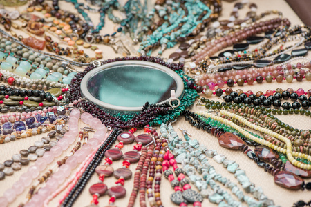 Gemstone bracelets and necklaces made of malachite, rose quartz, larimar, mahogany obsidian, unakite, amethyst, chalcedony, green jasper stones and crystals laying on linen tablecloth around mirror