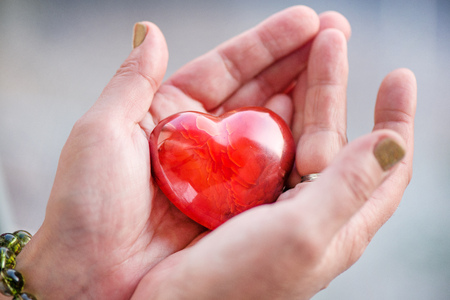 Mothers love. Womans hands holding heart shaped gemstone. Healthy lifestyle concept