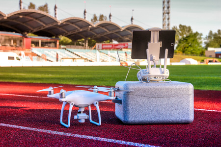 Drone is ready for take off. White quadcopter with four motors and propellers standing in large stadium next to its carry box and remote controller with touchpad, waiting for work. Aerial footage Stock Photo - 87659692