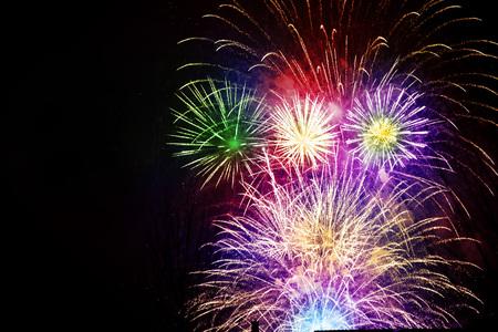 Kleurrijk, mooi vuurwerk aan de nachtelijke hemel boven de stad. Nieuwjaarsviering. Wazige, vallende sterren.
