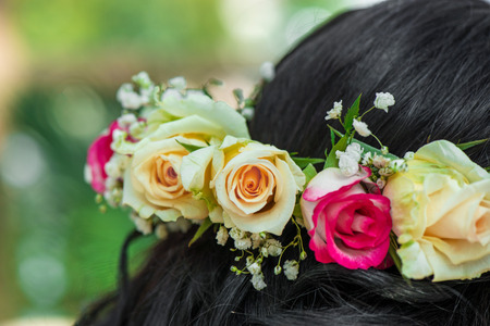 Female hair with beautiful colorful flower crown. Cheerful bride and bridesmaids party before wedding
