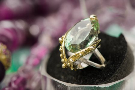 Macro shot of silver engagement ring with green amethyst gemstone, on colorful, sparkling background. Green Amethyst is a very spiritual stone. Stone of happiness and wisdom