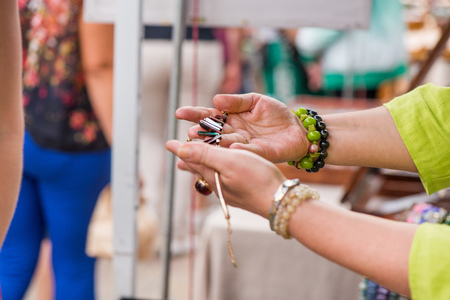 Woman with luxury gemstone rings and bracelets selling expensive jewelry. Shot of reaching hand for a necklace