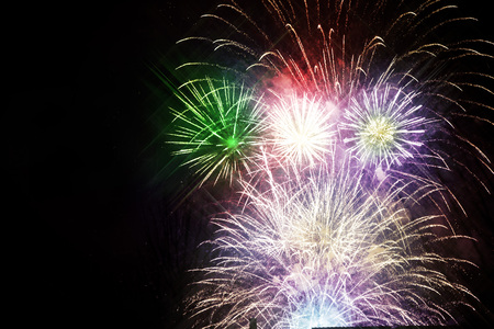 Colorful, beautiful fireworks on the night sky over the city. New Year celebration. Blurry, falling stars.