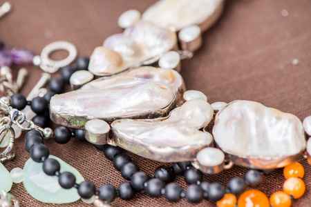 Biwa pearl necklace laying on natural brown linen tablecloth. Black onyx and agate gemstones around.Healing, powerful energy for crystal therapy treatments. Esoteric background Stock Photo