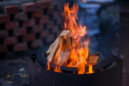 Burning bonfire with soft glowing flame and sparkles flying all around. Romantic summer evening. Preparing grill for barbecue party Banque d'images