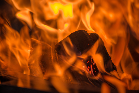 Burning bonfire with soft glowing flame and sparkles flying all around. Romantic summer evening. Preparing grill for barbecue party Stock Photo