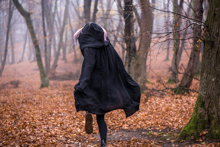 Girl in black hood running away from danger deep in dark forest. Thick fog all around. Scary autumn scene Stock Photo