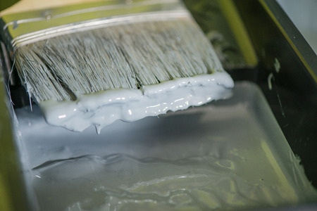 Macro shot of dripping grey color. Tray liner and paint during renovation in house Stok Fotoğraf