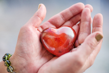 Mothers love. Womans hands holding heart shaped gemstone. Healthy lifestyle concept - taking care of heart health. Healing crystals with powerful energy