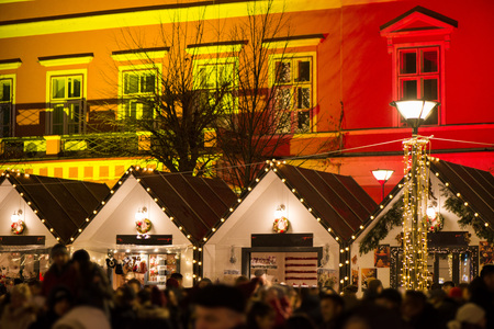 Crowded Christmas market in city center, decorated wooden huts with glowing lights. People enjoying event and searching for gifts. Beautiful Christmas background