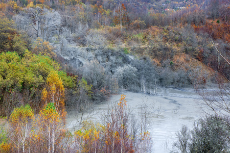 Polluted lake with copper mining residuals. Drowned and destroyed village. Autumn background with colorful and trees