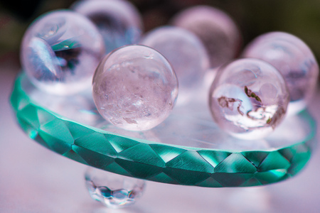 Macro shot of transparent crystal balls with colorful ornaments and sun reflections in it, on turquoise glass pad. Fortune telling. Love, money, luck, success.