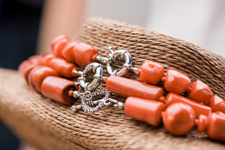 Silver clasp on a red coral stone and crystal necklace. Beautiful, polished gemstones on natural rustic background, Healing, powerful energy for crystal therapy treatments, reiki. Esoteric background Stock Photo