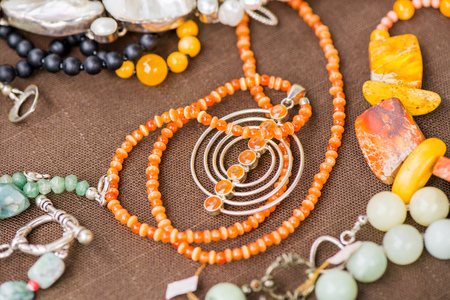 Serdolik (carnelian) stone necklace laying on natural brown linen tablecloth. Yashma, orange jasper, onyx gemstones around. Healing, powerful energy for crystal therapy treatments. Esoteric background Stock Photo