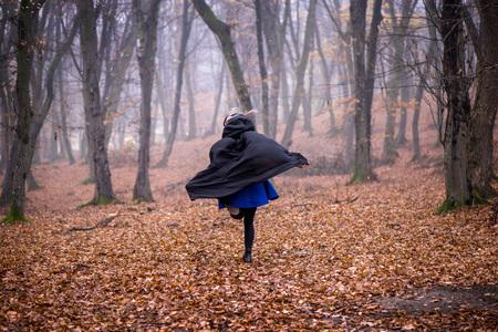 Meisje in zwarte kap die vanaf gevaar diep in donker bos loopt. Dikke mist rondom. Enge herfstscène Stockfoto