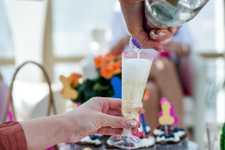 Group of girls celebrating - pouring champagne in glasses and drinking. Cheerful bride and bridesmaids party before wedding. Women having fun.  Colorful, funny and obscene background