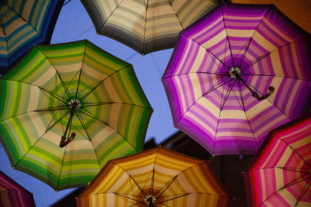 Night shot of colorful umbrellas in small street in middle of city on blue evening sky background. Romantic walk in rainy day