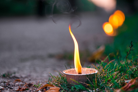 Macro shot of lit candle burning with soft glowing flame and smoke on evening background. Candle path at the park close to the seaside during the Night of ancient lights