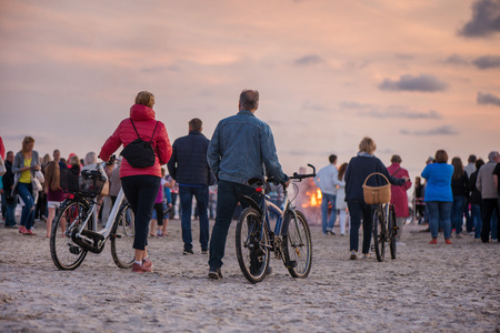Romantic bonfire night at seaside during sunset. People gathering together to celebrate Night of ancient lights. Large burning campfire with soft glowing flame and sparkles in the background.