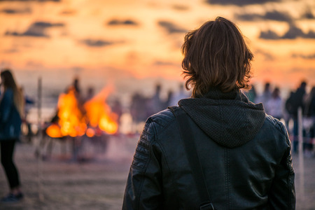 Lonely young man looking at the sunset and waiting his love. Romantic bonfire night at seaside. People gathering together to celebrate Night of ancient lights. Large burning campfire with glowing flame Stock Photo