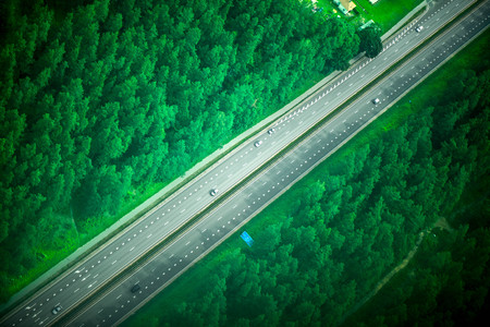 Aerial shot from plane of highway road and foggy forest on both sides. Cars are driving fast Reklamní fotografie
